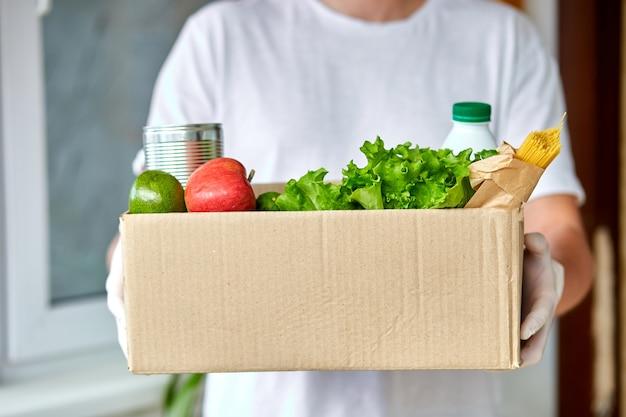 Doe vrijwilligerswerk in een wit beschermend masker en een donatiebox voor handschoenen. koeriersman met verpakkingsdoos met voedsel