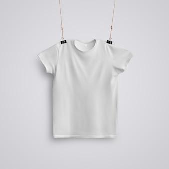 Doek sjabloon. een leeg t-shirt hangend aan zwarte metalen clips met ambachtelijk touw op een witte studioachtergrond. voorste positie. mockup klaar voor gebruik in uw ontwerp.