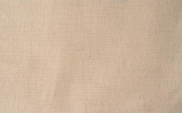 Doekpatroon in natuurlijke tint. abstracte achtergrond en textuur voor ontwerp. close-up van linnen textiel, beige achtergrond, stof textuur in hoge resolutie