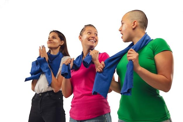 Doel. vrouwelijke voetbalfans die voor favoriete sportteam juichen met heldere emoties die op witte studioachtergrond worden geïsoleerd.