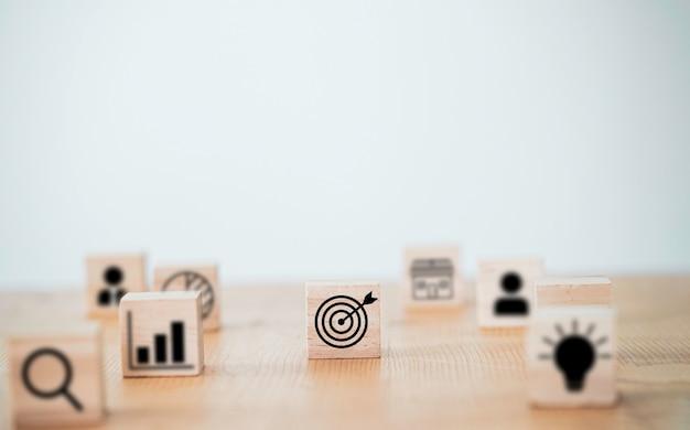 Doelbord met pijlafdrukscherm op houten kubusblok om een objectief doel en investeringsdoel in te stellen.