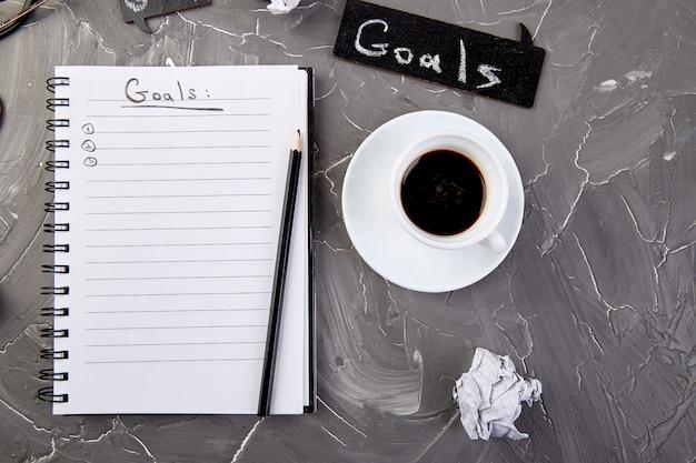 Doelen als memo op notitieboekje met idee, verfrommeld papier, kopje koffie