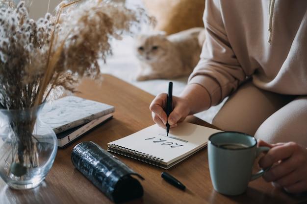 Doelen nieuwjaar resolutie planning vrouw schrijven in notitieblok met tekst laden op de tafel in Premium Foto