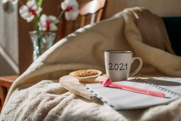 Doelen nieuwjaarsresolutie begin met het plannen van beker met tekst en open notitieblokpen op bed in zonlichtbeker