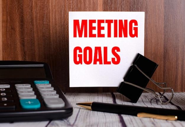 Doelen vergaderen is geschreven op een witte kaart op een houten oppervlak naast een rekenmachine en een pen