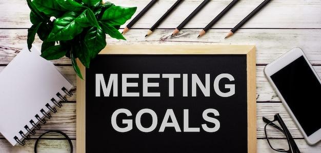 Doelen vergaderen is in het wit geschreven op een zwart bord naast een telefoon, notitieblok, bril, potloden en een groene plant