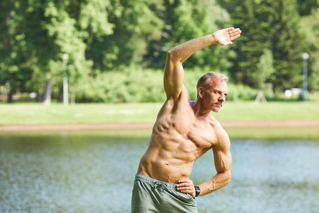 Doelgerichte volwassen man met perfect lichaam warming-up oefening doen tijdens het trainen in het park