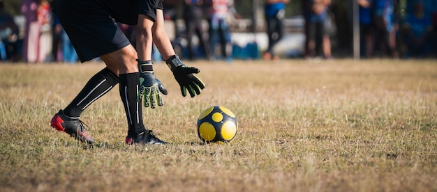 Doelman vangt de bal op het voetbalveld