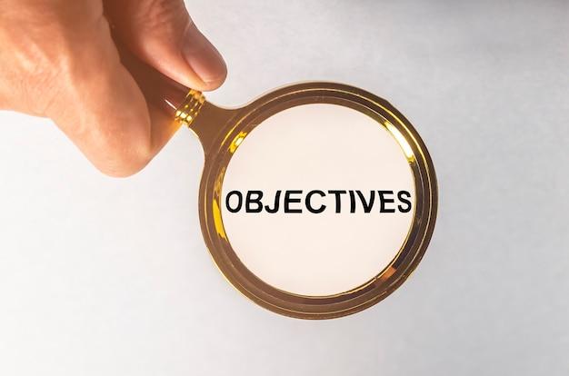 Doelstellingen woord inscriptie door vergrootglas op financiële documenten, zakelijke doelen.