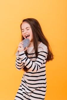 Doen alsof superster, klein meisje luistert naar muziek. muzikale opvoeding, zingende haarborstelmicrofoon en ontwikkelende stem.