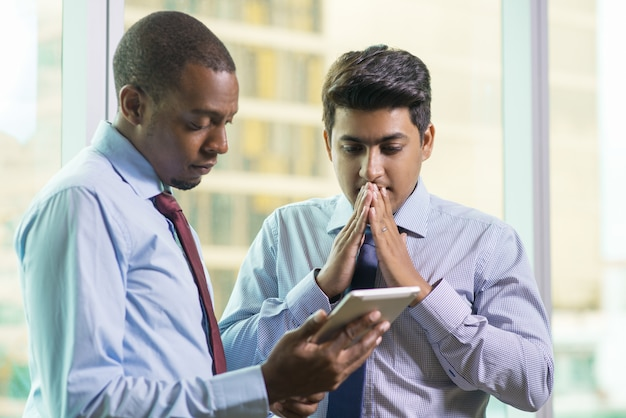 Doen schrikken biddende zakenman die e-mail op tabletcomputer lezen