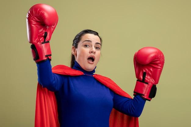 Doen schrikken jong superheromeisje die bokshandschoenen dragen die handen opheffen die op olijfgroene achtergrond worden geïsoleerd