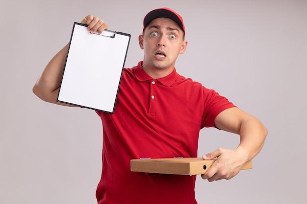 Doen schrikken jonge bezorger die eenvormig met glb draagt die klembord met pizzadoos houdt die op witte muur wordt geïsoleerd