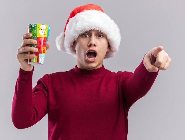 Doen schrikken jonge kerel die kerstmishoed draagt die de punten van de kerstmiskop houdt die op witte muur worden geïsoleerd
