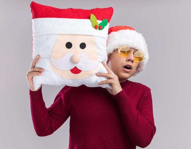 Doen schrikken jonge kerel die kerstmishoed met glazen draagt die kerstmishoofdkussen houdt dat op witte achtergrond wordt geïsoleerd