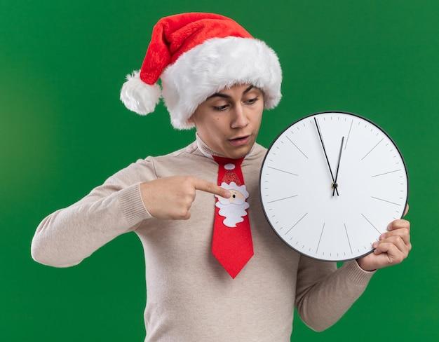 Doen schrikken jonge kerel met kerstmuts met stropdas bedrijf en wijst op muurklok geïsoleerd op groene muur