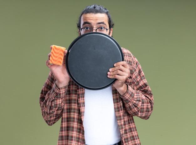Doen schrikken jonge knappe schoonmaakster die de spons van de t-shirtholding en bedekt gezicht met dienblad draagt dat op olijfgroene muur wordt geïsoleerd