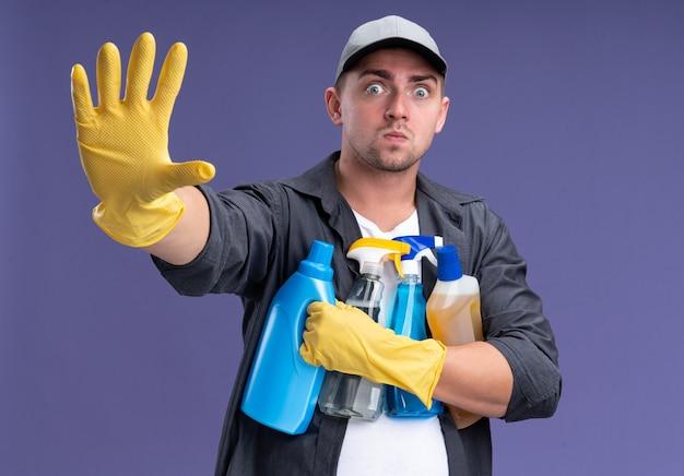 Doen schrikken jonge knappe schoonmaakster die t-shirt met pet en handschoenen draagt die schoonmaakgereedschap houden die hand uitsteken die op paarse muur wordt geïsoleerd