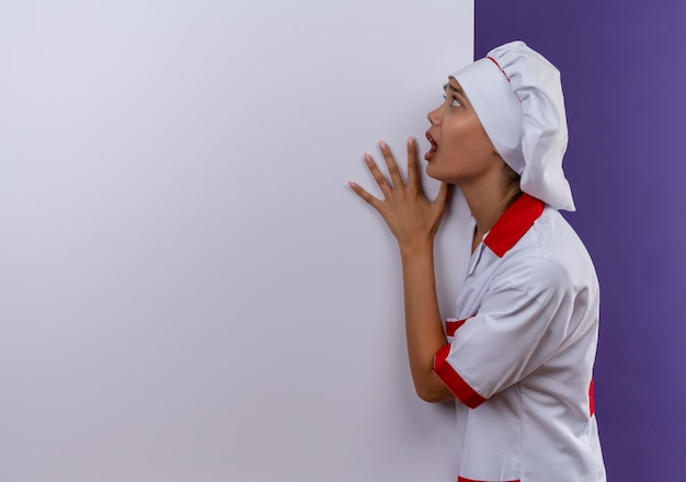 Doen schrikken jonge kokvrouw die eenvormige chef-kok draagt die witte muur op geïsoleerde achtergrond met exemplaarruimte houdt