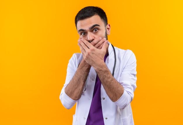 Doen schrikken jonge mannelijke arts die de behandelde mond van de stethoscoop medische toga op geïsoleerde gele achtergrond draagt