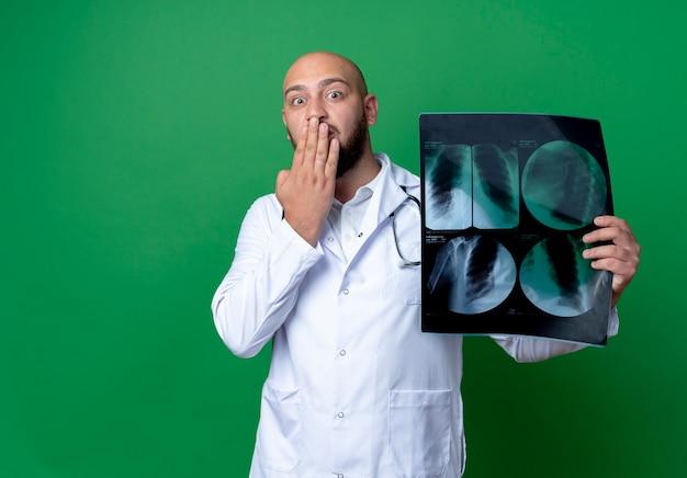 Doen schrikken jonge mannelijke arts die medische mantel en stethoscoop draagt die x-ray en behandelde mond met hand houdt die op groene achtergrond wordt geïsoleerd
