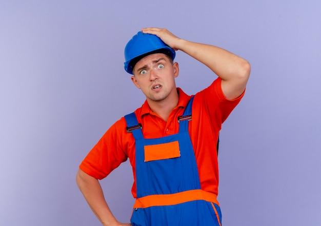Doen schrikken jonge mannelijke bouwer die uniform en veiligheidshelm draagt die hand op hoofd op paars zetten