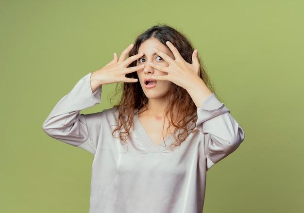 Doen schrikken jonge mooie vrouwelijke beambte bedekt gezicht met handen geïsoleerd op olijfgroen