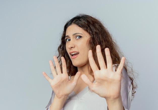 Doen schrikken jonge mooie vrouwelijke beambte die eindegebaar toont dat op witte muur wordt geïsoleerd