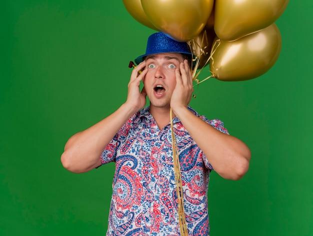 Doen schrikken jonge partij kerel die blauwe hoed draagt die ballons houdt en handen op wangen zet die op groen worden geïsoleerd