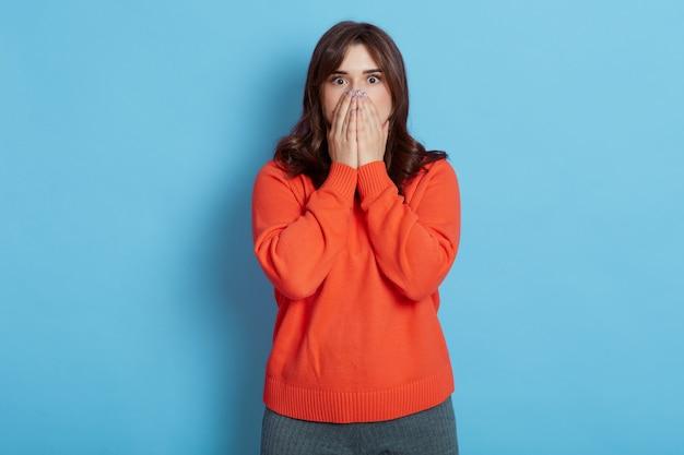 Doen schrikken jonge volwassen donkerharige vrouw, gekleed in casual oranje trui
