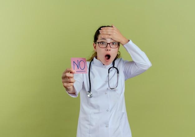 Doen schrikken jonge vrouwelijke arts die medische mantel en stethoscoop met bril draagt die document nota houdt die hand op geïsoleerd voorhoofd zet