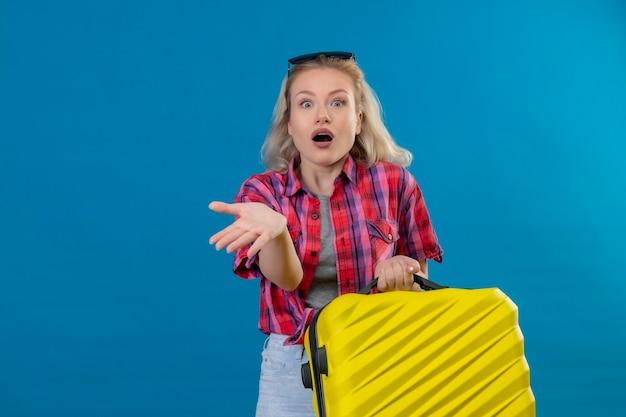 Doen schrikken jonge vrouwelijke reiziger die een rood overhemd en een bril op het hoofd draagt en de koffer wijst naar de zijkant op geïsoleerde blauwe muur