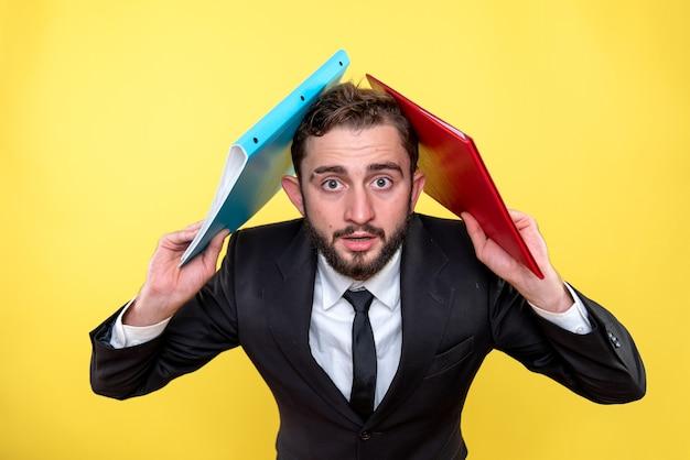 Doen schrikken jonge zakenman die twee documenten op zijn hoofd over geel houdt
