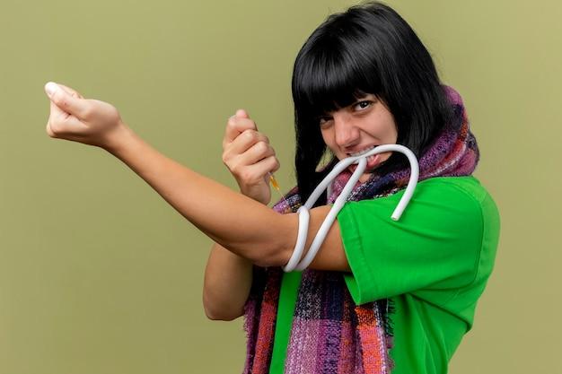 Doen schrikken jonge zieke vrouw die sjaal aanscherping harnas met tanden houdt die spuit doet die injectie doet aan zichzelf kijkend naar voorzijde geïsoleerd op oranje muur