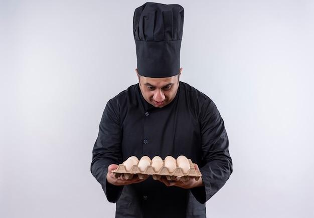 Doen schrikken mannelijke kok van middelbare leeftijd in eenvormige chef-kok die partij eieren in zijn hand bekijkt