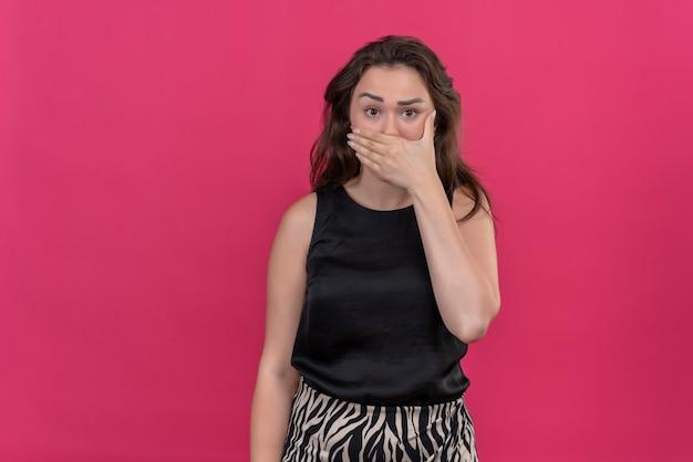 Doen schrikken vrouw, gekleed in zwart onderhemd dat haar gezichtshand op roze muur bedekt