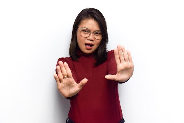 Doen stop gebaar van jonge mooie aziatische vrouwen jurk rood shirt geïsoleerd op een witte achtergrond