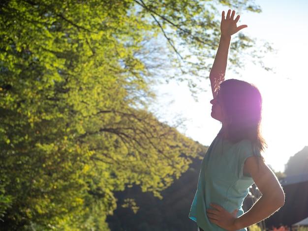 Doet een warming-up buiten een jonge vrouw met een blauw t-shirt