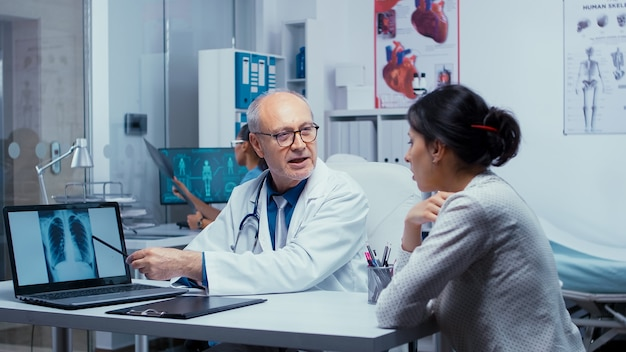 Dokter analyseert röntgenscanresultaten op laptop met jonge vrouwelijke patiënt. oudere senior ervaren arts in gesprek met patiënt over longen, röntgenpneumonie, kanker, consultatie van onderzoeksspecialisten