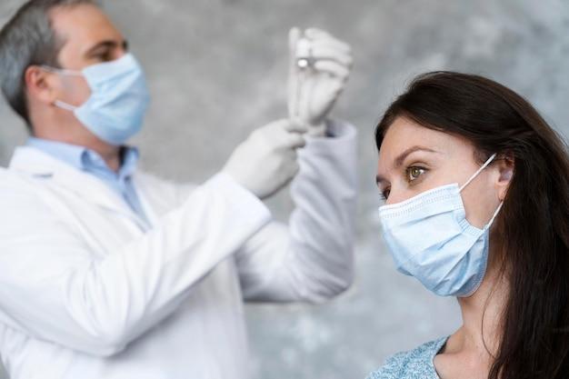Dokter bereidt vaccin voor vrouwelijke patiënt voor