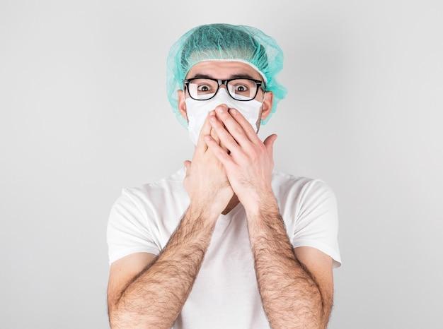 Dokter-chirurg in wit medisch masker en een medische pet staat met verbazing op witte achtergrond