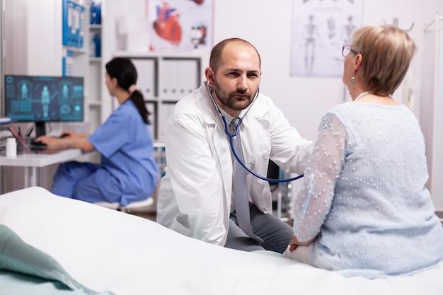 Dokter controleert ademhalingsprobleem van zieke senior vrouw in het ziekenhuis