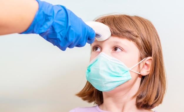 Dokter controleert de lichaamstemperatuur van het meisje met behulp van een infrarood voorhoofdthermometer