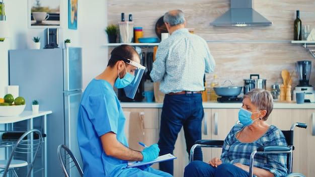 Dokter controleert lichaamstemperatuur van gehandicapte senior vrouw in rolstoel tijdens huisbezoek met behulp van infrarood thermometer. gehandicapte bejaarde krijgt aanbeveling van maatschappelijk werker