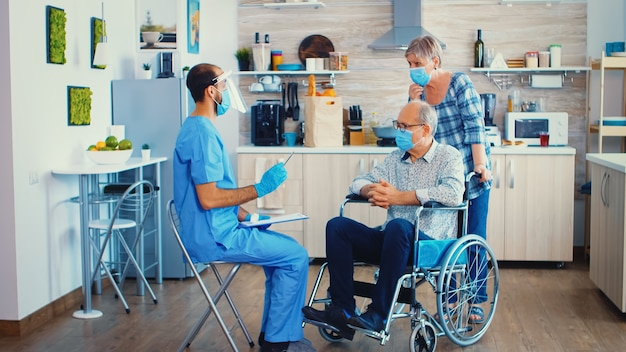 Dokter controleert tijdens huisbezoek gehandicapte patiënt in rolstoeltemperatuur met thermometerpistool tegen covid-19. gehandicapte bejaarde krijgt aanbeveling van maatschappelijk werker
