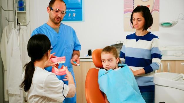 Dokter die aan het kind de juiste mondhygiëne toont met behulp van een mock-up van het skelet van de tanden. tandarts met monster van menselijke kaak met tandenborstel in stomatologie kantoor werken met man assistent.
