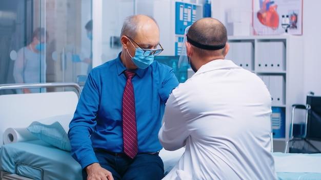 Dokter die bloeddruk meet aan senior oude gepensioneerde man patiënt tijdens covid-19 gezondheidszorg crisis wereldwijde pandemie in modern privé ziekenhuis of kliniek. het dragen van beschermende uitrusting onderzoeksruimte