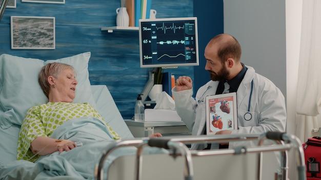 Dokter die cardiovasculair beeld op tablet toont aan zieke patiënt