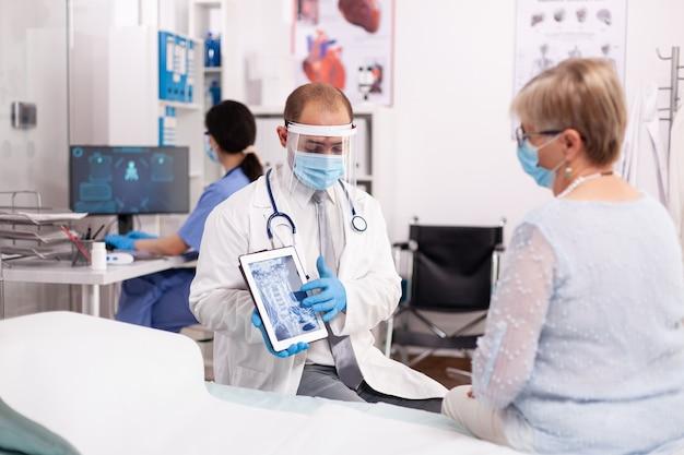 Dokter die de behandeling uitlegt aan een oudere vrouw die naar een röntgenfoto wijst op een tablet-pc die een gezichtsmasker draagt