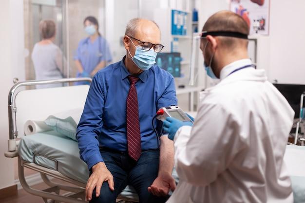 Dokter die de bloeddruk van een oudere patiënt meet in de spreekkamer van het ziekenhuis tijdens het covid19-onderzoek